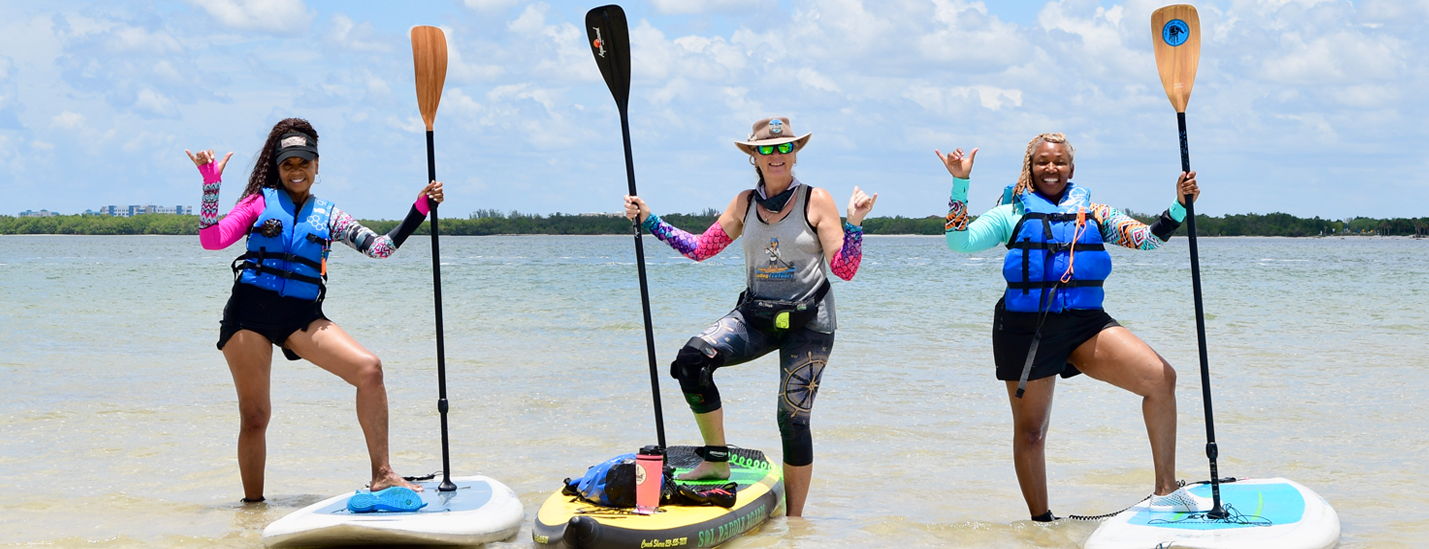 coach sheree with clients paddle boarding - image